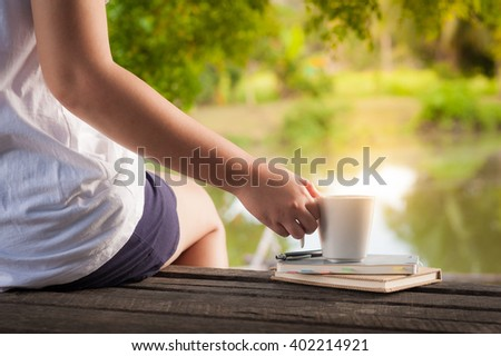 Woman right hand holding coffee cup beside notebooks on rustic wood bench with rural lake view in background in morning time on weekend - stock photo