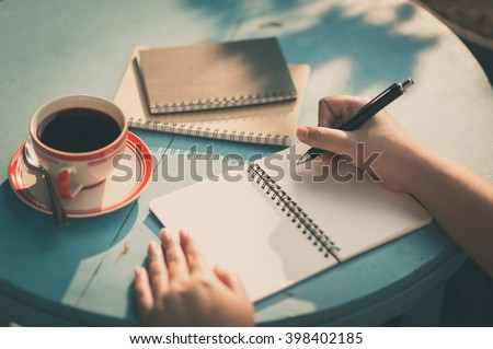 Woman right hand writing journal on small notebook at outdoor area in cafe with morning scene and vintage filter effect - stock photo
