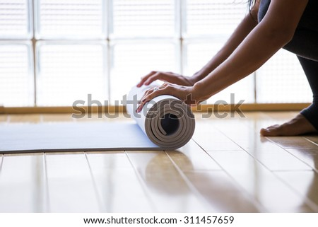 Woman rolling her mat after a yoga class - stock photo