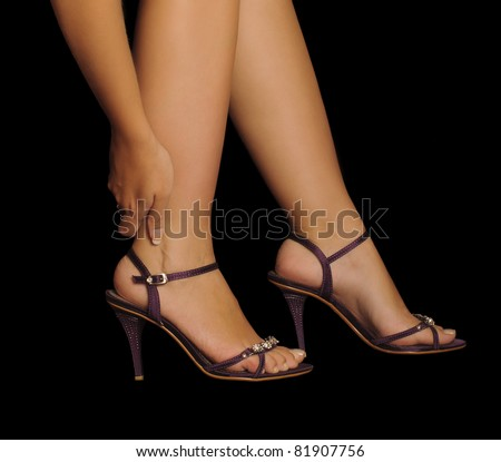 Woman rubbing her leg, pain from wearing high heels, stilettos, beautiful feet and sexy legs - stock photo