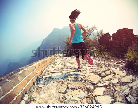 woman runner athlete running on trail at chinese great wall . woman fitness jogging workout wellness concept.  - stock photo