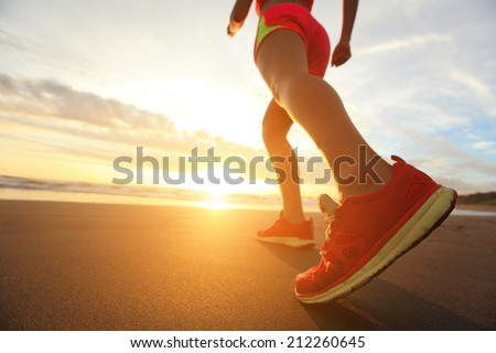 Woman Runner feet running on the beach at sunrise closeup on shoe. woman fitness sunrise jog workout wellness concept. asian - stock photo