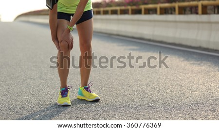 woman runner hold her injured leg on road - stock photo