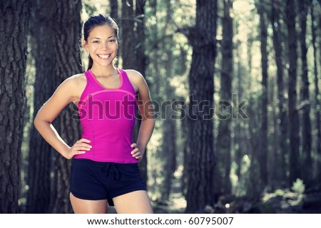 Woman runner in forest. Portrait of female runner taking a break from running in beautiful forest with lots of mood / atmosphere and copy space. Beautiful young female athlete. - stock photo