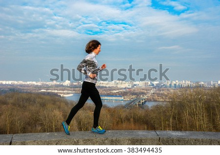 Woman runner jogging with beautiful city view, running and exercising outdoors  - stock photo