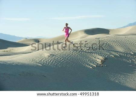 Woman runner on sand dunes - stock photo