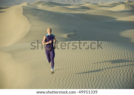 Woman runner on sand dunes - stock photo