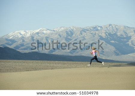 Woman runner on sand dunes with mountains.