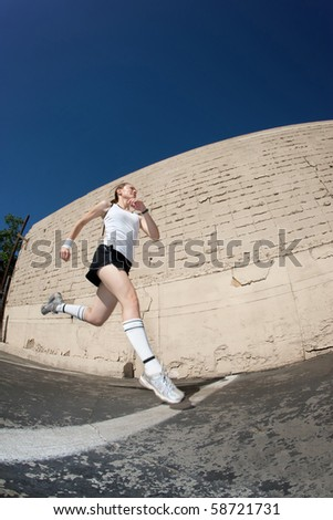 Woman runner practices sprinting towards the finish line. - stock photo