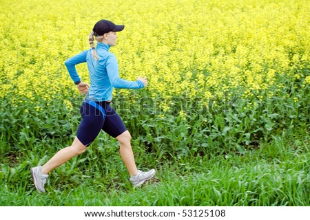 Woman runner running outdoors in spring, jogging and fitness - stock photo