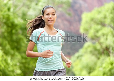 Woman runner running training living healthy fitness sport lifestyle. Active female athlete jogging outside smiling happy with aspirations. Beautiful young mixed race Asian Caucasian girl in her 20s. - stock photo