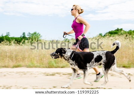 Woman runner running with dog on country road in summer nature, fitness and exercising outdoors, motion blur. - stock photo