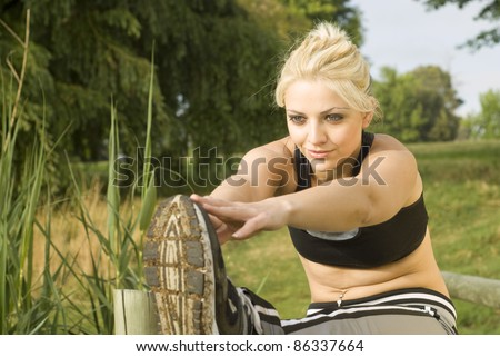 Woman runner stretching both arms forward on wooden bridge - stock photo
