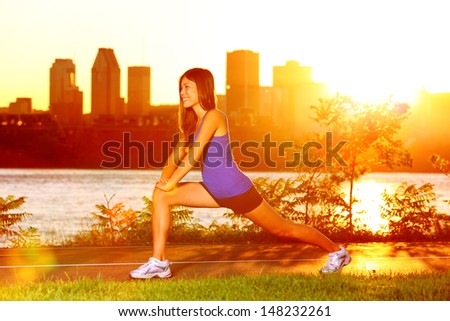 Woman runner stretching legs after running training in sunshine at sunset. Fit female jogger athlete training outside in Montreal, Canada, Quebec. - stock photo