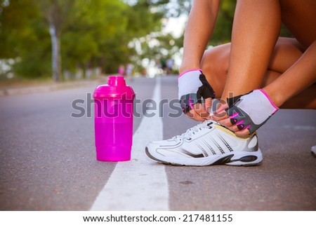 Woman runner tying sport shoes - stock photo