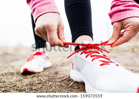 Woman runner tying sport shoes. Walking or running legs, autumn adventure and exercising outdoors. Motivation and inspiration fitness concept outside. - stock photo