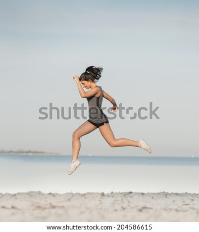Woman running alone at beautiful sunrise at the beach. Summer sport and freedom concept. Athlete training on dusk. - stock photo