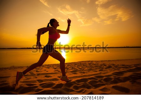 Woman running alone at beautiful sunset in the beach. Summer sport and freedom concept.