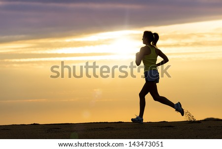 Woman running alone at beautiful sunset in the beach. Summer sport and freedom concept. Athlete training  on dusk. - stock photo