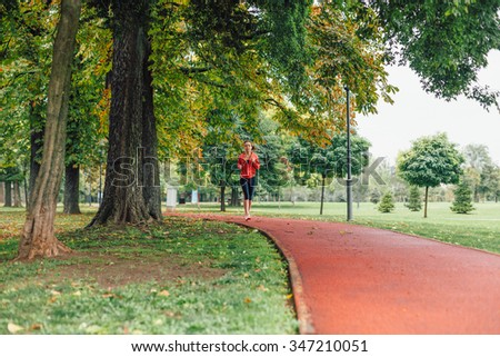 Woman running at the park in autumn - stock photo