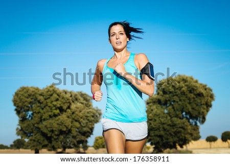 Woman running cross trail in countryside on summer. Sweaty fit girl exercising. - stock photo