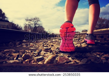 woman running down railroad tracks during the sunlight with retro instagram filter (shallow depth of field) - stock photo