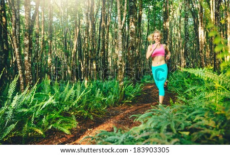 Woman Running in Nature. Trail Running in Forest. Active Healthy Lifestyle Fitness Concept. - stock photo