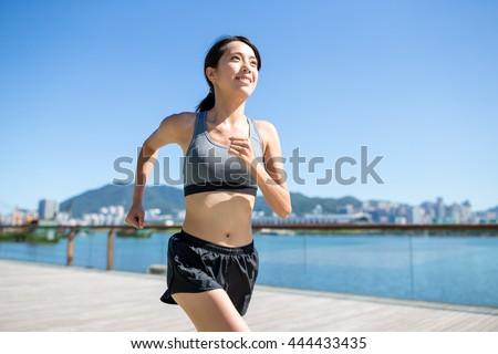 Woman running in seaside boardwalk - stock photo