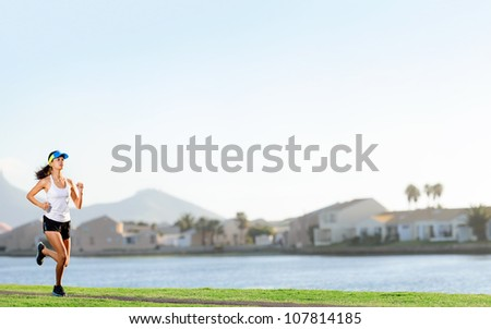 Woman running in suburb park for fitness and wellness exercise. healthy lifestyle active panorama with copyspace - stock photo