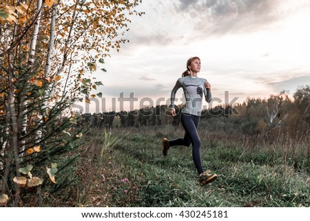 Woman running in the autumn forest