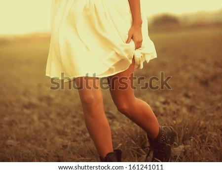 Woman running in the field in autumn - stock photo