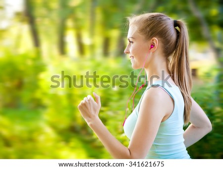 Woman running in the forest and listening to music