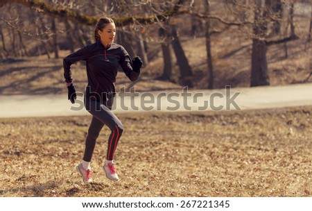 Woman running in the morning in nature while being positive and motivated - stock photo