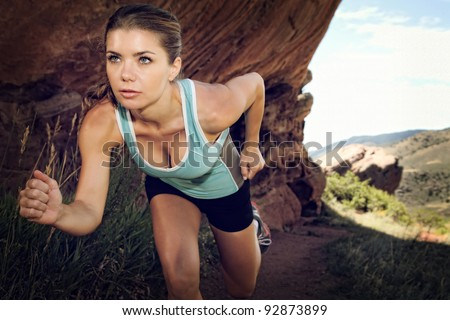 Woman running in the mountains - stock photo