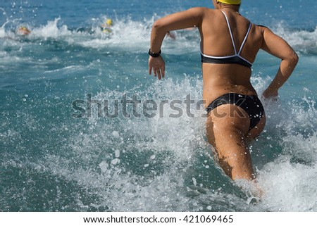 Woman running in water in the swimming competition - stock photo