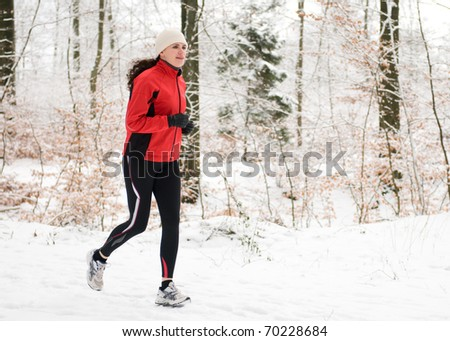 Woman running in winter forest - stock photo