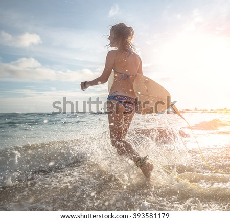 Woman running into the sea with surf board - stock photo