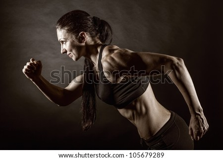 Woman running on a dark background. Side view - stock photo