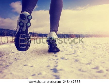 woman running on a snowy country road with view of the snow covered mountains in background with instagram filter (shallow depth of field) - stock photo