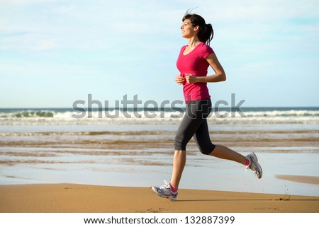 Woman running on beach at sunset. Beautiful fitness caucasian girl exercising outdoors on sea background. Caucasian fit model. - stock photo