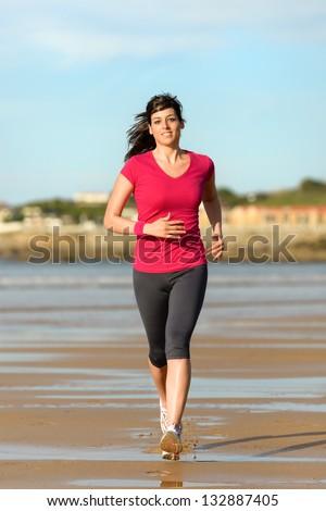 Woman running on beach at sunset. Beautiful fitness caucasian girl exercising outdoors on sea background.  Playa de San Lorenzo, Gijon, Spain. - stock photo