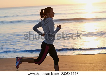 woman running on beach in morning sunrise fitness workout sport - stock photo
