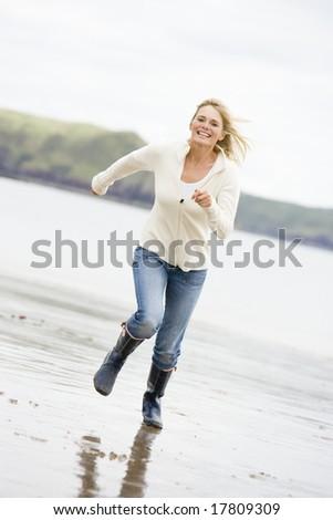 Woman running on beach smiling - stock photo