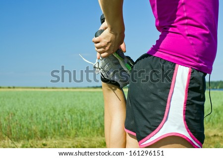 Woman running on country road and exercising stretching outdoors in summer nature. Female runner sport and fitness. - stock photo
