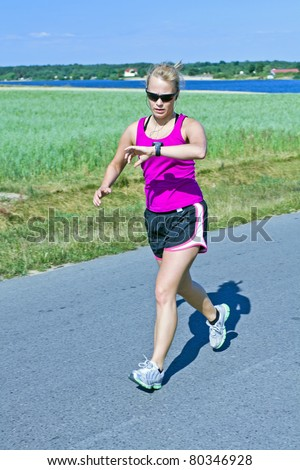 Woman running on country road, checking a watch heart rate monitor and listen to music. Training and exercising in summer nature beautiful outdoors - stock photo