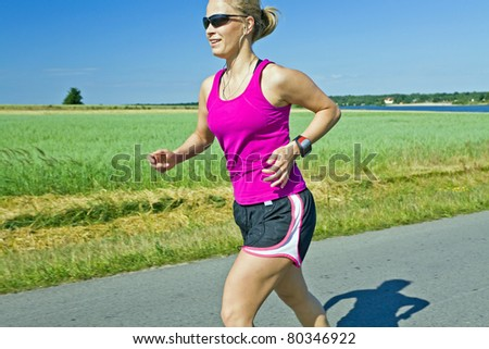 Woman running on country road, meadow and summer landscape - stock photo