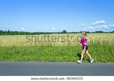 Woman running on country road over blue sky and landscape and meadow - stock photo