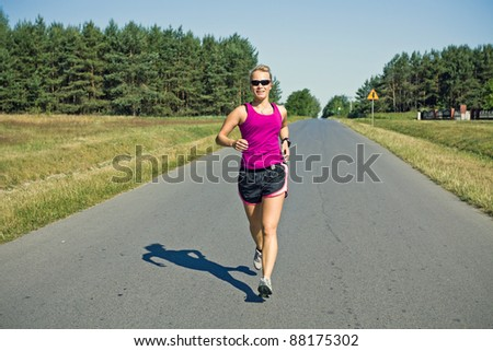 Woman running on country road, sport training in summer nature - stock photo