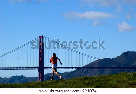 woman running on grass with golden gate bridge in distance - stock photo