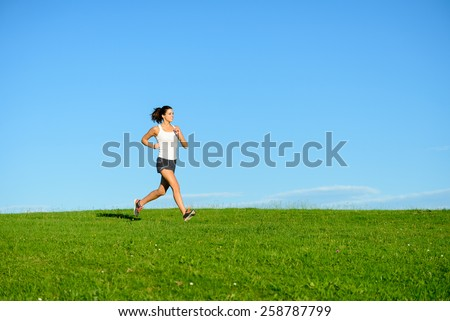 Woman running on summer or spring grass field. Female athlete exercising outdoor. Brunette fit sporty model training towards clear blue sky background.